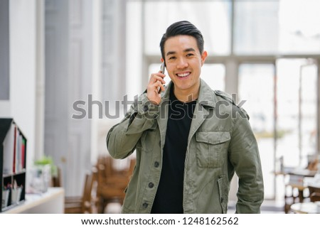A young, confident and good-looking Chinese Asian man is speaking on his smartphone. He is comfortably dressed in casual clothing and is smiling.