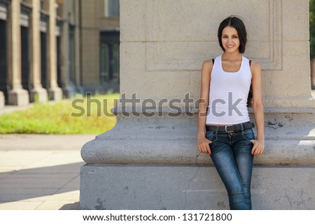 A young, confident girl stands near a wall, in waiting