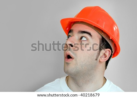 A young construction worker isolated over silver that is looking up at something in amazement.
