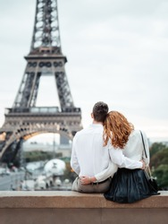 A young couple (a guy and a red-haired girl) in white shirts sit and hug against the backdrop of the Eiffel tower in Paris. Romantic trip to Europe.