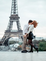 A young couple (a guy and a red-haired girl) of elite College students in white shirts embrace against the backdrop of the Eiffel tower in Paris. Student trip to Europe.