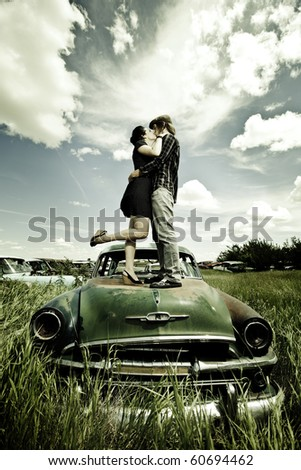 A young couple are kissing on a old broken car in a field./Young Couple Kissing on Old Broken Car