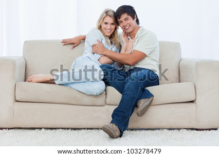 A young couple are sitting down on a couch embracing each other