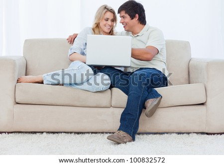 A young couple are sitting on a couch with a laptop