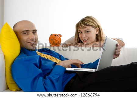 A young couple at home reviewing their finances with a piggy bank and laptop computer.