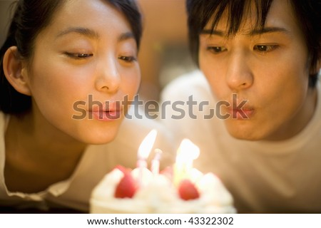 A young couple blowing off birthday candle