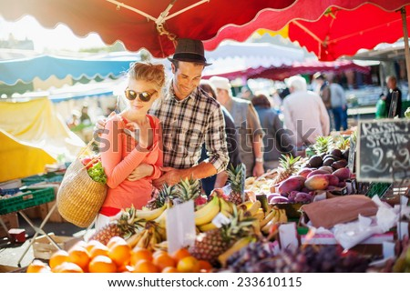 a young couple buying fruits and vegetables in a market on a sunny morning, the young woman carries a basket