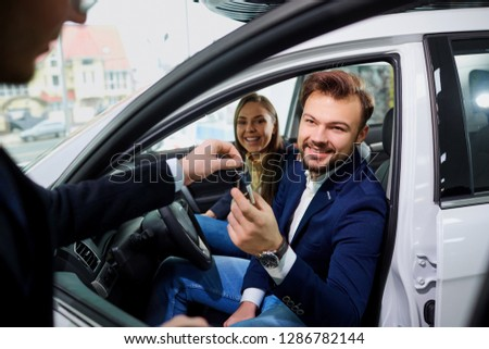 A young couple buys a car in the auto salon