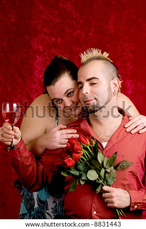 A young couple celebrate with wine and flowers.