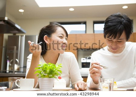 A young couple chatting and eating in the kitchen