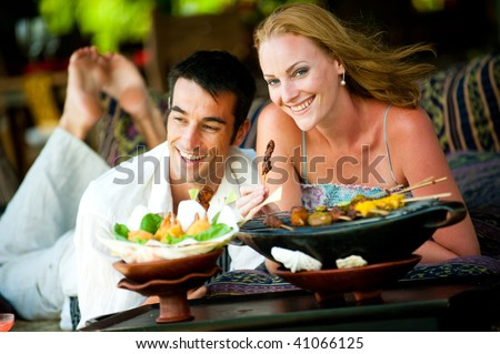 A young couple enjoying a relaxed lunch whilst on vacation