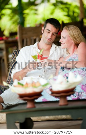 A young couple enjoying cocktails before lunch whilst on vacation