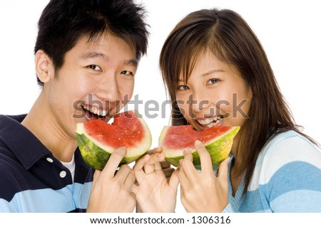 A young couple enjoying eating watermelon