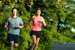 A young couple go jogging around a park with each other, smiling. - horizontally framed