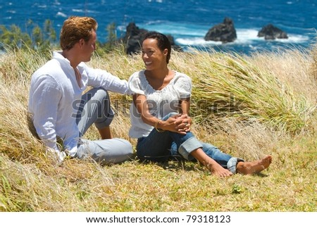 A young couple have a conversation while sitting in the tall grass on a cliffside overlooking the ocean in Maui, Hawaii.