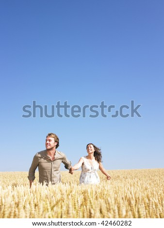 A young couple holding hands and walking through wheat field. Vertically framed shot.