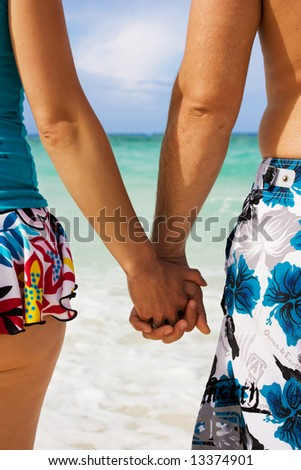 A young couple holding hands on the beach in Cuba