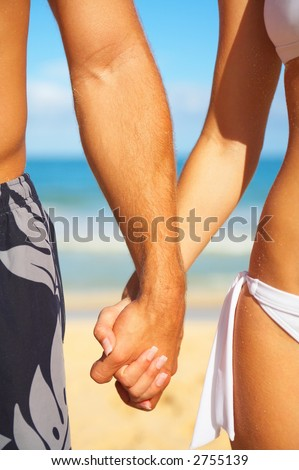 stock photo : A young couple holding hands on the beach in Hawaii