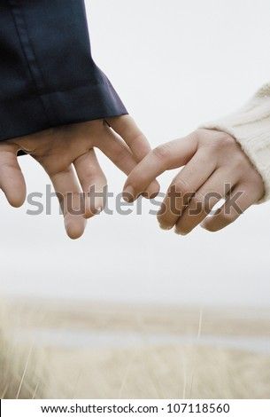 a young couple holding hands, outdoors