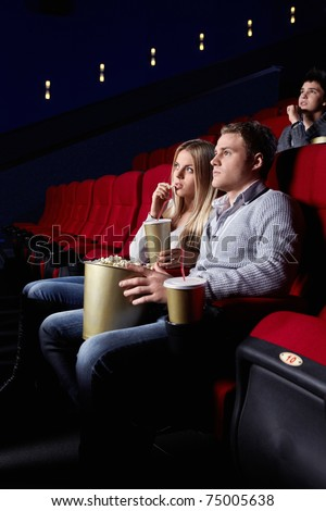 A young couple in a movie theater