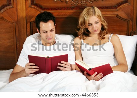 a young couple in bed reading a book