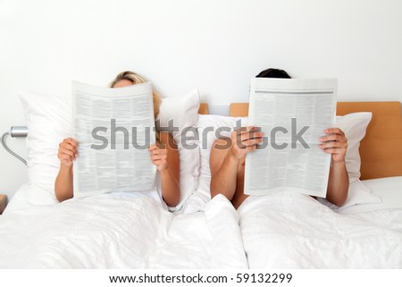 A young couple in bed reading a newspaper. Information and news