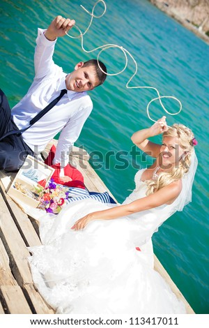 "A young couple in love bride and groom posing on the bridge background blue sea in their wedding day in summer.Together hold a decorated wire word ""LOVE"". Enjoy a moment of happiness and love."