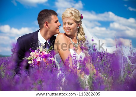A young couple in love bride and groom, wedding day in summer. Enjoy a moment of happiness and love in a lavender field. Bride in a luxurious wedding dress on a background bright blue sky with clouds.