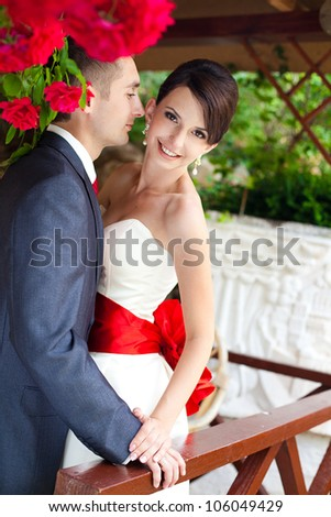 A young couple in love bride and groom with a bouquet, posing in their wedding day. Enjoy a moment of happiness and love.