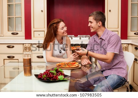 a young couple in love eating pizza