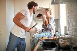 A young couple in love having good time while preparing a breakfast together on a beautiful morning. Cooking, together, kitchen, relationship