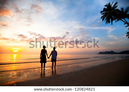 A young couple in love holding hands at sunset at the seaside