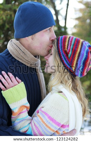 a young couple in love in the park in winter