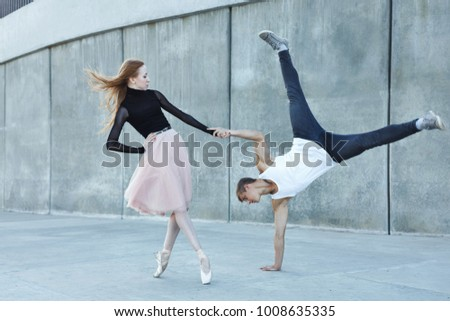 A young couple in love passionately dances on a city street. Dancer and sportsman Parkour. Balance and stunts in the dance. Meshenie classical and modern dance. #1008635335