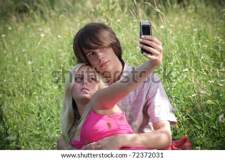 A young couple in nature using their mobile phone to take self portrait