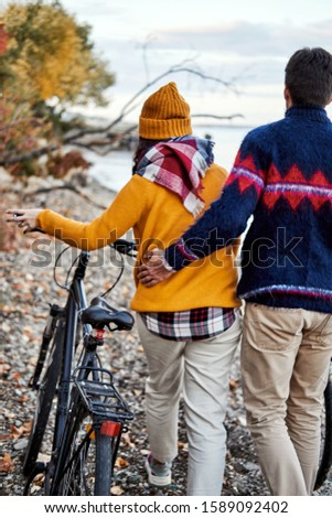 A young couple in sweaters with bicycles walks and walks along the shore, after a bike ride