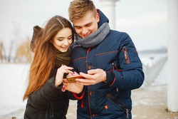 A young couple in winter jackets and scarves standing in a snowy park and use the phone