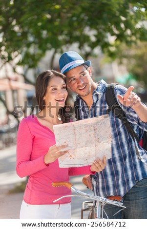 A young couple is looking for direction. A woman is holding a map, while a grey hair man is pointing some direction, holding a bike. The man with a beard is wearing a blue hat and a black backpack.