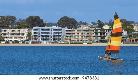 A young couple is sailing towards condominiums in Mission Bay, San Diego, California. A perfect metaphor for sailing to first home ownership through the sea of life.