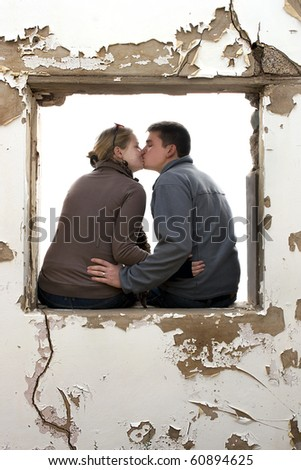 A young couple kissing in a window frame of an old building, blank background