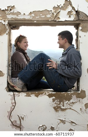 a young couple laughing together and having fun inside a window frame of an old building