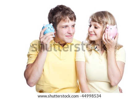 A young couple listening to their piggy banks, can be used for finance or saving concept