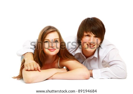 A young couple lying on the floor, isolated on white background
