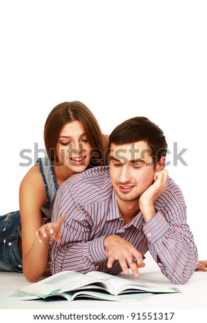 A young couple lying on the floor isolated on white background