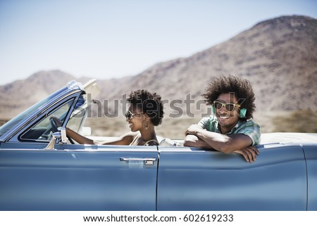 A young couple, man and woman in a pale blue convertible on the open road #602619233