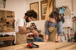 A young couple of carpenters working together in a small carpentry workshop designing a new home furniture piece crafting out of timber. Young entrepreneurs running their own business in Lisbon