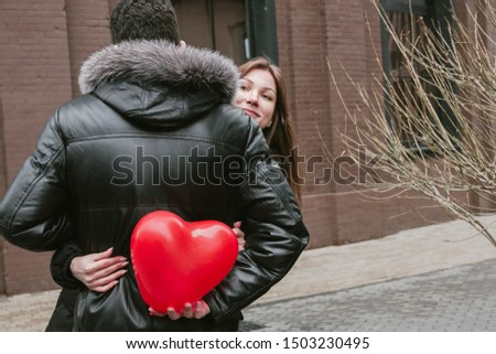 A young couple of young people in love holding a red ball in the shape of a heart, hugging each other and experiencing tender feelings, Valentine's Day.