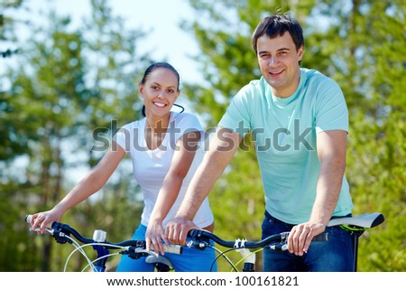 A young couple on bicycles looking at camera and smiling