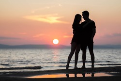 A young couple on the sea at sunset. A guy and a girl at sunset.
