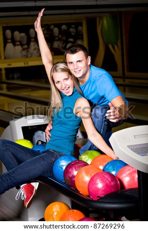 a young couple playing bowling